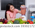 woman making smoothies with blender in kitchen 39302172