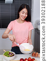 woman cooking and whisking eggs in a bowl in kitchen 39302188