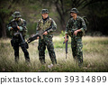 Squad of soldiers patrolling across forest area. 39314899
