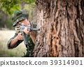 Private millitary holding gun aiming behind a tree 39314901