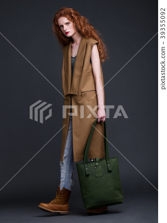 Red hair fashion model holding large leather bag 39355092