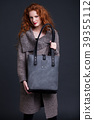 Red hair fashion model holding large leather bag 39355112