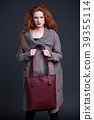 Red hair fashion model holding large leather bag 39355114