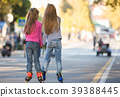 Two girls girlfriends rollerblading on the mall, rear view 39388445