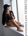 Sexy brunette in black baseball cap on window sill 39389372