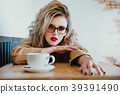 Beautiful fashionable stylish girl sits in a cafe 39391490
