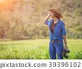 Woman wear hat and hold binocular in grass field 39396102