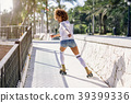 Black woman, afro hairstyle, on roller skates riding near the be 39399336