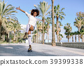 Black woman on roller skates rollerblading in beach promenade wi 39399338