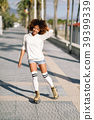 Black woman on roller skates rollerblading in beach promenade wi 39399339