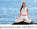 Young woman doing yoga in the beach wearing white clothes 39399373