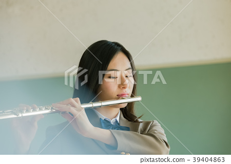 Female student blowing a flute 39404863
