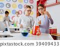Pleasant schoolchildren examining test tube with 39409433