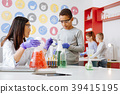 Caring chemistry teacher adding agent to students 39415195