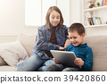 Two kids with gadgets on couch at home 39420860