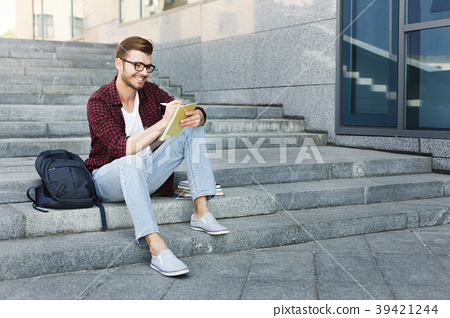 Attractive student making notes sitting on stairs 39421244