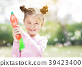 happy little girl playing water guns in the park 39423400