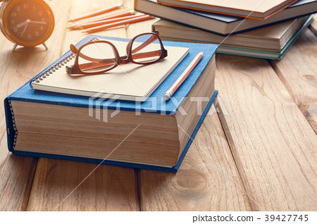 Books and glasses on a wooden table desk 39427745
