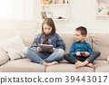 Two kids with gadgets on couch at home 39443017