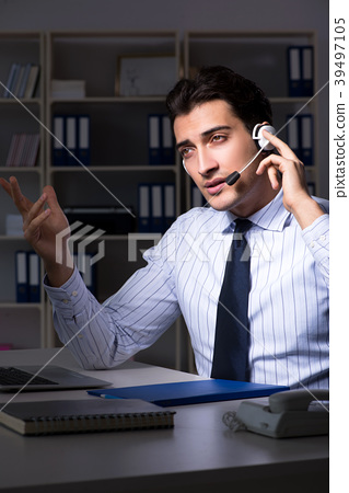 Tired and exhausted helpdesk operator during night 39497105