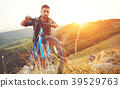 cycling. young man with bicycle on nature in mountains 39529763