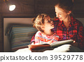 mother and child reading book in bed before going to sleep . 39529778