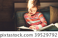 girl child reads book in bed 39529792