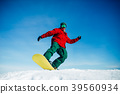 Snowboarder in glasses poses with board in hands 39560934