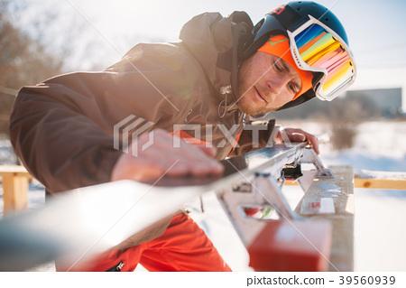 Male skier checks skis before skiing, winter sport 39560939