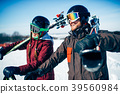 Male and female skiers poses with skis and poles 39560984