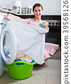 housewife with basket of linen near washing machine indoors 39568126
