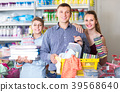 couple and teenager with household goods purchase in the store 39568640