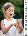 Portrait of surprised girl looking at mobile phone 39569364