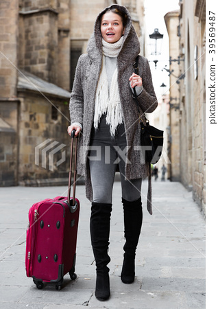 young girl in hood and coat with baggage 39569487