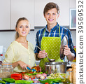 man and woman standing near table in domestic kitchen 39569532