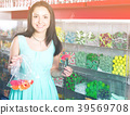 Pretty girl in sweets store picks up candies in bag 39569708