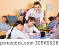 Group of school kids with pens and notebooks studying in classroom with teacher 39569928