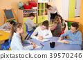 boys and girls sitting and teacher helping drawing 39570246
