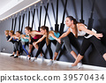 Females exercising wall yoga with straps in studio 39570434