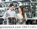Couple buying pans in shop cookware. 39571301