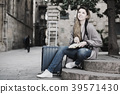 traveling girl searching for the direction using a booklet in the town 39571430