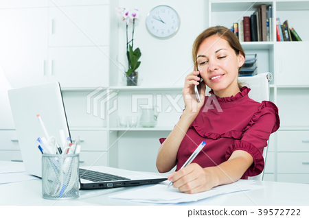 attentive female employee answering on phone and taking notes 39572722