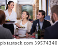 Waitress with dishes serving man and female 39574340