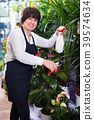 Seller tending yucca palm trees in flower shop 39574634