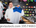 Sporty male is choosing new T-shirt for tennis in the store. 39574663