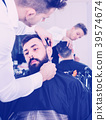 Male hairdresser accurately cutting beard of client 39574674