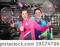 Sporty young couple in sportwear is demonstraiting new rocket and balls for tennis in the store 39574796