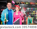 Young female with male are standing in sportwear with new racket for padel and tennis in the speciality store 39574898