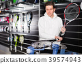Male master is pulling racket for tennis in the store. 39574943