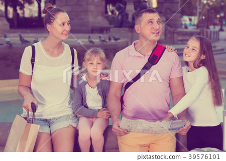 Adult family of four visiting sights with map 39576101